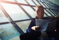 Business Frau mit Papieren schaut aus Fenster