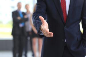 Businessmann streckt seine rechte Hand aus