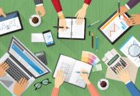 Kreatives Team am Schreibtisch mit Laptop, Notizblock und Tablet