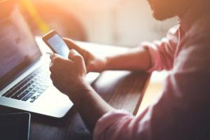 Mann im Hemd am Schreibtisch mit Laptop und Smartphone