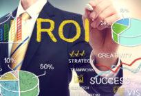 Businessmann, der ROI (return on investment) auf Screen schreibt