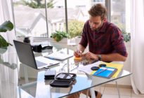 Junger Businessmann, der am Schreibtisch arbeitet