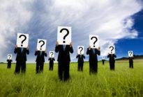 Gruppe von Business-Männern, die Schild mit Fragezeichen hochhalten