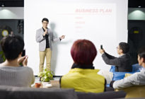Junger, asiatischer Businessmann präsentiert Gruppe Businessplan