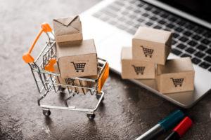 Symbol für E-Commerce mit Laptop, Paketen und Einkaufswagen