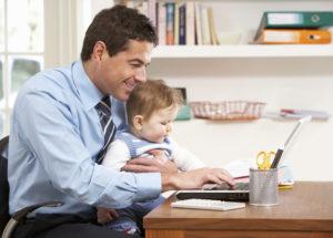 Businessmann mit Baby am Laptop zuhause
