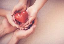 Vier Hände, die rotes Herz halten