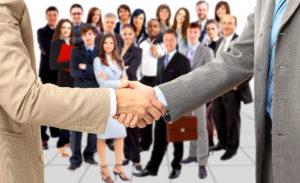 Zwei Businesshände schütteln sich, im Hintergrund Belegschaft