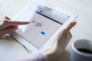 Hände mit Tablet und Google-Website