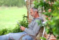 Älterer Mann auf einer Bank mit Tablet