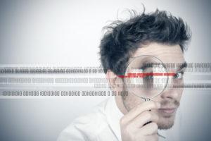Junger Mann mit Lupe auf Virussuche