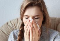 Junge Frau schneuzt sich die Nase