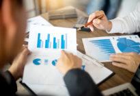 Businessmänner arbeiten an einem Tisch mit Grafiken