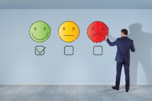 Businessman, der Emojis zur Kundenzufriedenheit malt