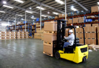 Logistik: Staplerfahrer mit Kartons
