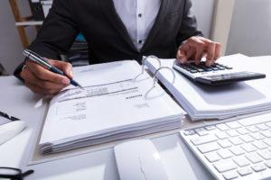 Hände, die Rechnungen mit Taschenrechner kontrollieren