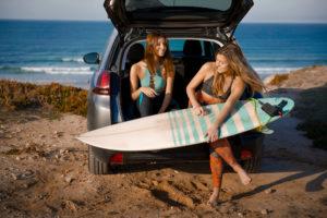Zwei Surferinnen mit Surfbrett und Auto