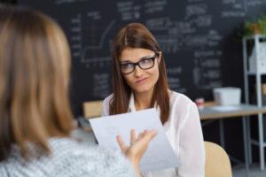 Unbeeindruckte Frau hört Kollegin zu