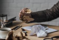 Männliche Hand zerknüllt Papier auf Schreibtisch