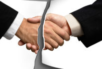 Zwei Businesshände schütteln sich, dazwischen befindet sich ein Riss