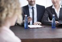 Zwei Recruiter, die am Tisch einer Bewerberin gegenüber sitzen