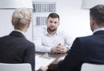 Zwei Recruiter, die Bewerber gegenüber am Tisch sitzen