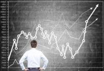 Businessmann steht vor Tafel mit Chart