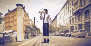 Marketing: Mann auf Straße schreit in Megaphone