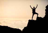 Mann besteigt Berg bei Sonnenuntergang