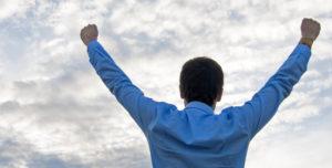 Erfolg: Mann streckt seine Arme in den Himmel