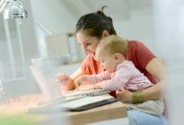 Businessfrau arbeitet mit Baby an Laptop