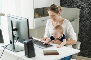 Frau arbeitet mit Baby am Computer Zuhause
