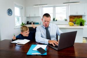 Mann und Junge beim Homeschooling während Corona