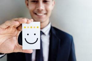 Businessmann, der Karte mit Smiley in der Hand hält