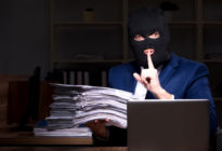 Mann mit Maske stiehlt Daten nachts aus Büro