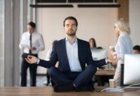 Businessmann meditiert auf Schreibtisch
