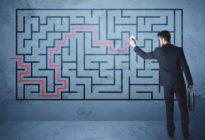 Geschäftsmann zeichnet auf Tafel mit Labyrinth