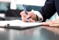 Frauenhand unterschreibt Dokument