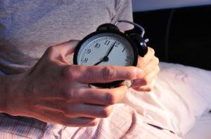 Junger Mann im Bett mit Wecker in der Hand