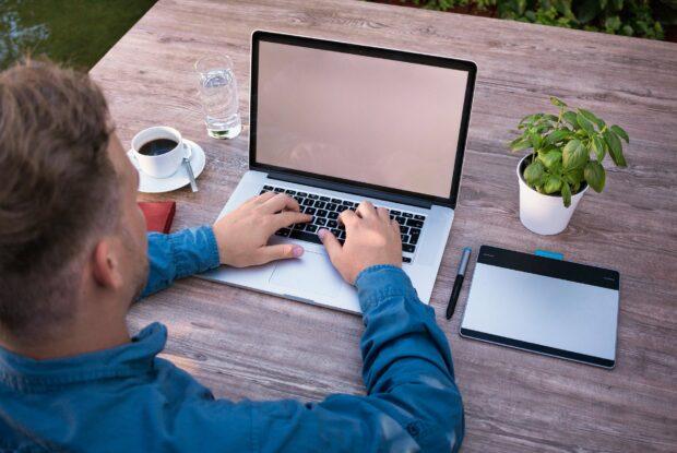 Junger Mann mit Laptop im Homeoffice