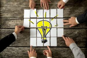 Hände, die Puzzle mit Glühleuchte zusammenlegen