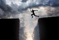 Mann, der über Felsspalten springt