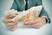 Mann mit Anzug zählt Eurogeldscheine
