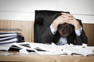 Frustrierter Businessmann mit Aktenberg