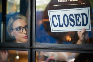 Shopbesitzerin hängt Closed-Schild auf