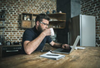 Junger Mann mit Laptop im Home-Office