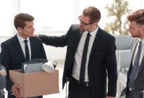 Gefeuerter Arbeitnehmer packt seine Sachen und verabschiedet sich von Kollegen