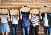 Junge Leute, die Sprechblasen in ihr Gesicht halten