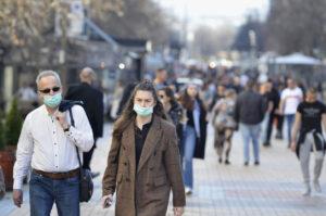 Mann und Frau mit Maske unter Passanten