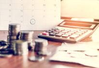 Rechner, Münzen und Kalender auf Schreibtisch